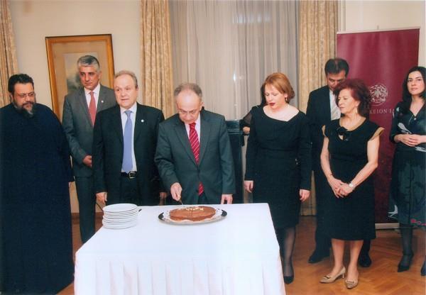 Ο επίτιμος δημότης Κορώνης Δ. Σιούφας περιστοιχισμένος από τα μέλη του Διοικητικού Συμβουλίου και τη δ/ντρια του ιδρύματος κόβει την πίττα